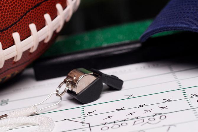 Schiedsrichterpfeife mit Football, Cap und Taktikgrafik auf Block