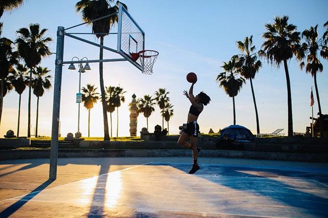 Frau wirft mit Basketball einen Korbleger.