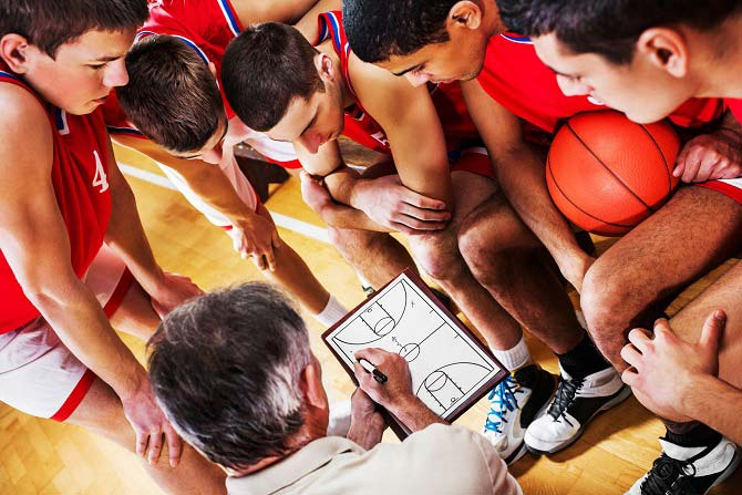The next play is being discussed during a time out by the basketball coach.