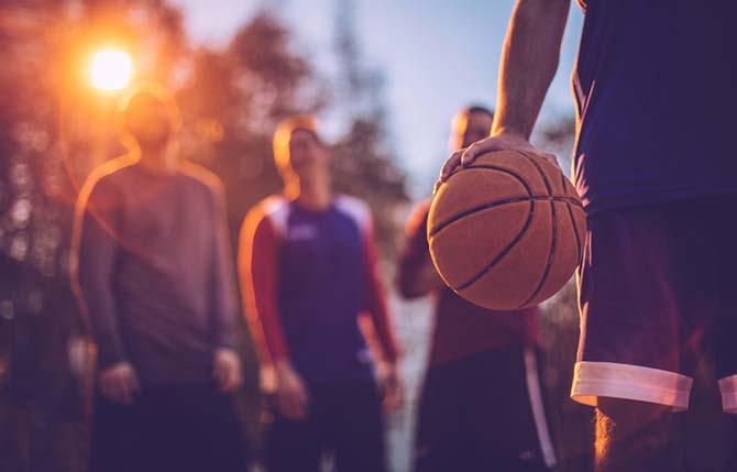 Basketballtraining: Mann in Basketballbekleidung hält Ball mit einer Hand