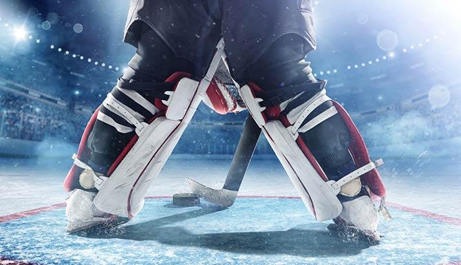 Beine eines Eishockey-Torwarts in der gefüllten Arena
