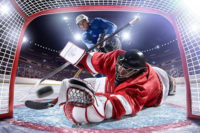 Eishockeyspieler beim Schuss ins Tor und Torhüter im Eishockeytor