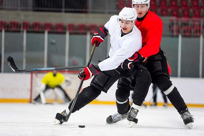 Gegnerische Eishockeystuermer im Wettkampf auf der Eisfläche