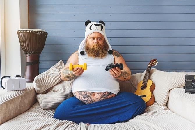Dicker Mann mit heraushängendem Bauch sitzt auf Couch und hält einen Game-Controller und eine Hantel in den zwei Händen