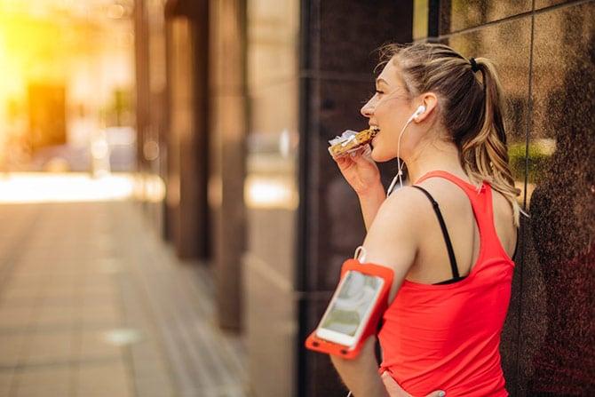 Sportlerin isst Riegel nach dem Joggen