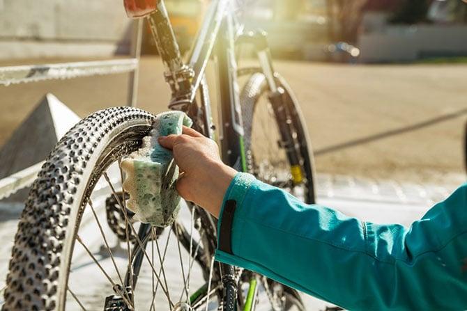Fahrrad wird mit Schaum und Schwamm geputzt