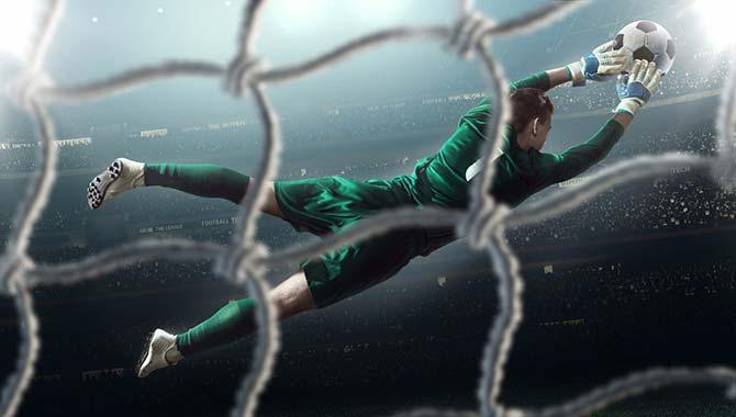 Torhüter im Fußball versucht im Sprung Ball zu halten