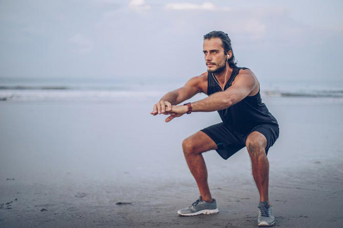 Sportler am Strand trainiert Grundübung