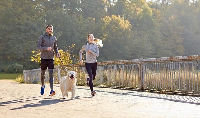 Paar beim Joggen mit Hund