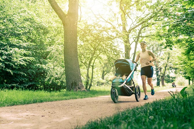 Mutter joggt mit Kind im Kinderwagen