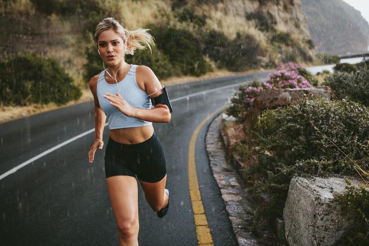 Läuferin auf Straße im Regen