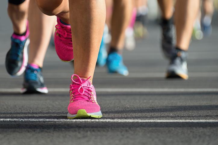 Beine mit Laufschuhen laufen auf Asphalt