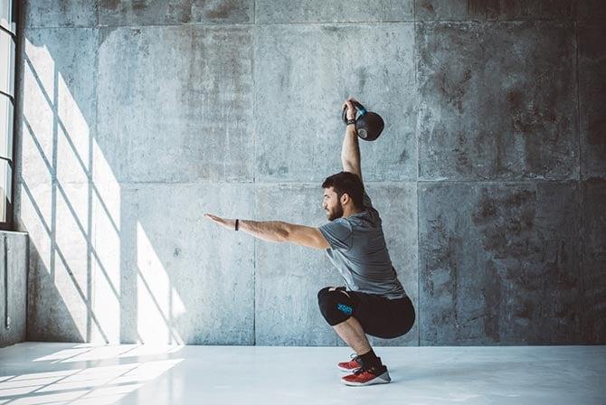 Mann trainiert Muskelfasertypen mit Gewicht.