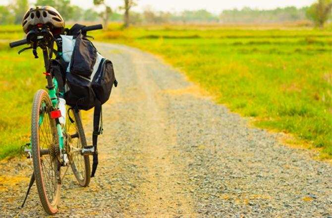 Bicycle with rucksack and helmet on gravel path