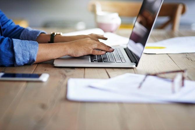 Frau schreibt Pressemitteilung für Verein am Laptop.