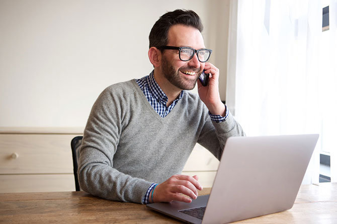 Mann im Homeoffice mit Laptop und Telefon