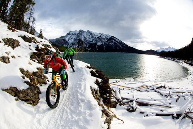 Radfahrer mit Fatbikes fahren im Schnee an einem See entlang