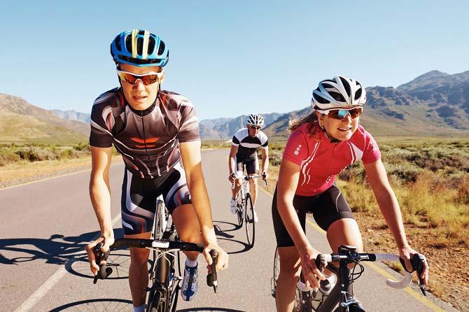 Dreiergruppe Radfahrer auf flacher Straße mit umliegenden Bergen