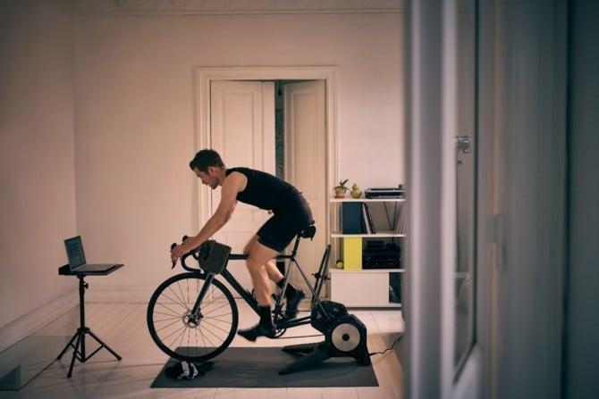 Mann bei Rennradtraining im Winter auf der Rolle