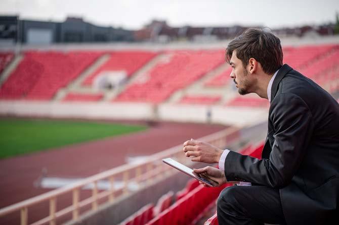 Sportdirektor werden: Mann im Anzug sitzt mit Tablet auf den Zuschauertribünen in einem Stadion