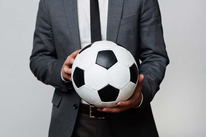 Sportmanager Fußball: Ausschnitt eines Anzugträgers mit Fußball in der Hand