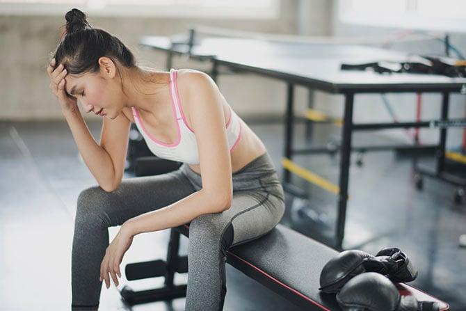 Frau nach dem Training mit Muskelkater
