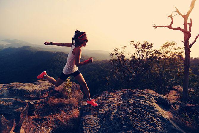 Frau im Sportoutfit rennt auf Berg