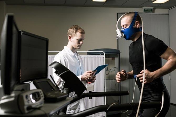 Trainingswissenschaft: Sportler mit Testgerät läuft auf Laufband, Arzt steht daneben