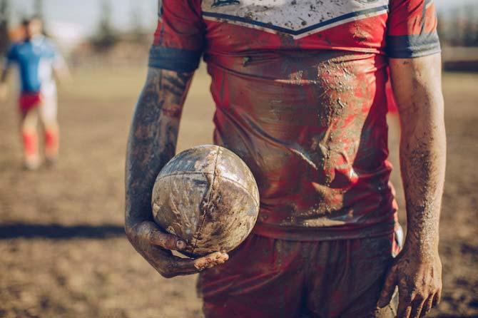 Sportler mit verschmutztem Football und stark matschig verschmutztem Trikot