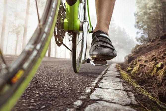 Pedale eines Rennrads auf der Straße