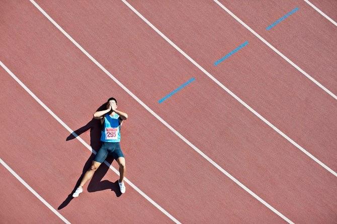 Erschöpfter Sportler liegt auf einer Laufbahn