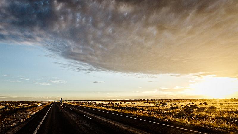 Fahrradfahrer in flacher Landschaft auf der Straße bei Sonnenuntergang