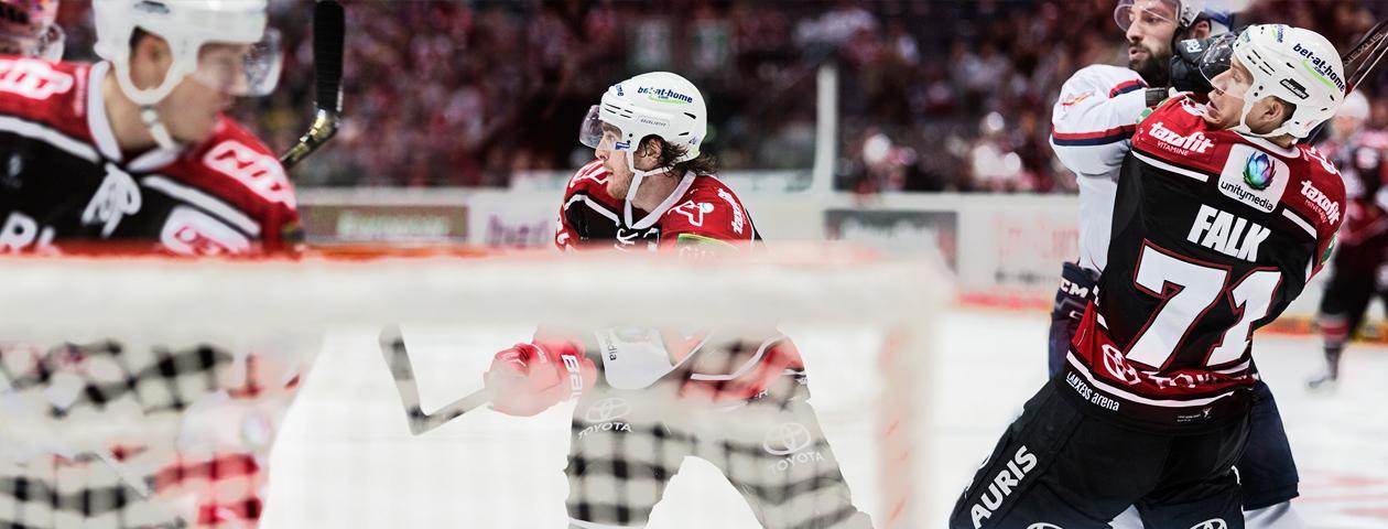 Eishockeyspieler der Kölner Haie in selbst gestalteten Eishockeytrikots und -hosen auf dem Eis mit Tor im Vordergrund