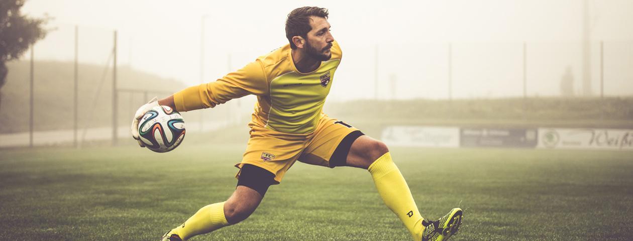 Torwart in selbst gestaltetem gelben Torwarttrikot wirft Fußball