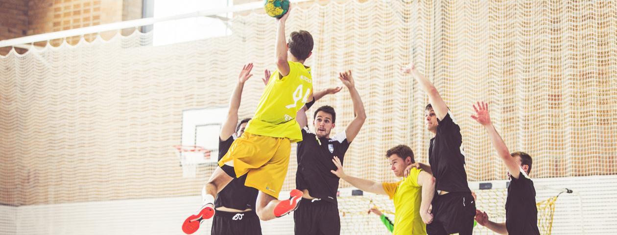 Handballer in selbst gestalteten Handballtrikotsätzen wehren Angriff ab