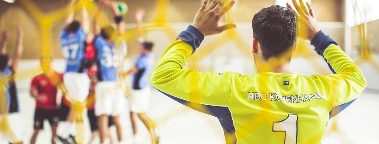 Giocatore di pallamano con maglia gialla personalizzata davanti alla porta a braccia alzate.