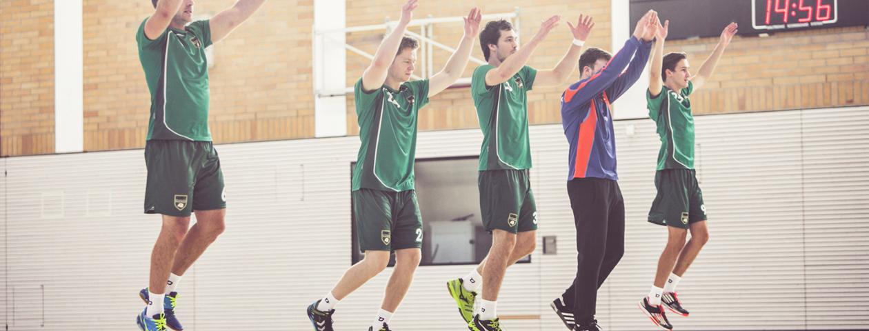 Handballtorwart mit leuchtend grünem selbst gestalteten Trikot lehnt lachend am Tor