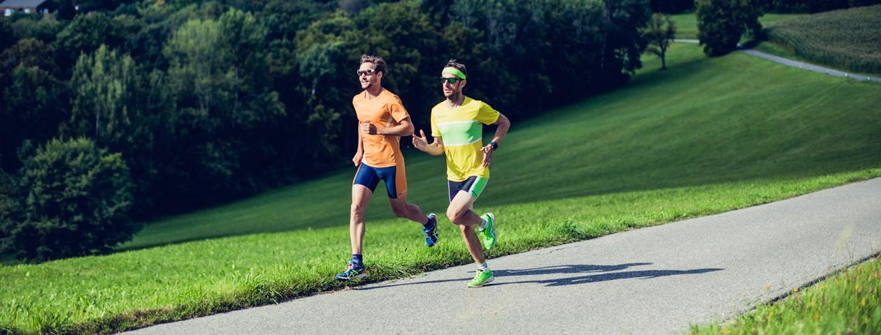Zwei Jogger in bunter selbst gestalteter Laufbekleidung auf einer Straße im Grünen
