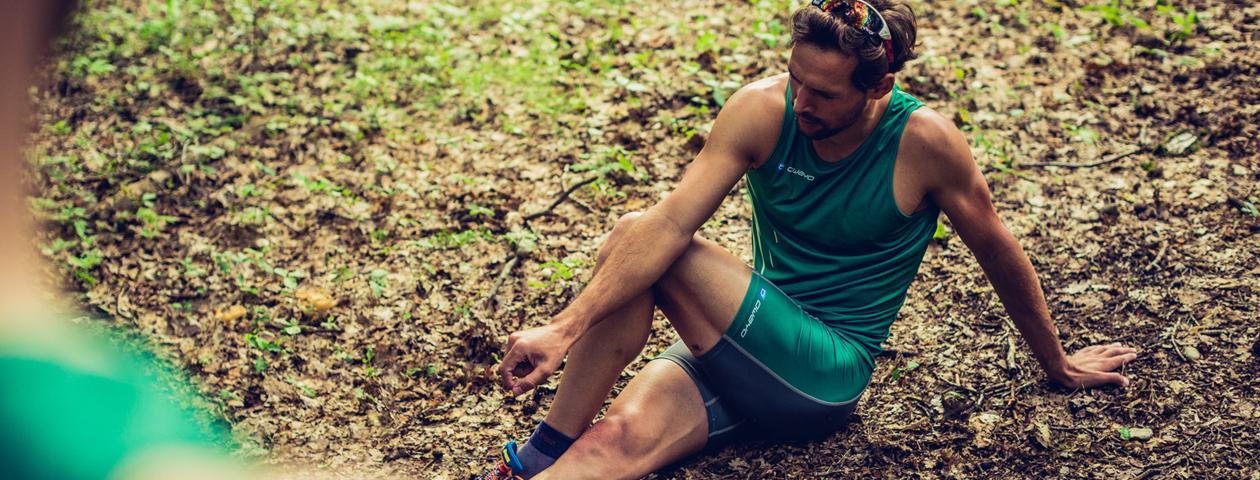 Läufer in grünem individualisierten Lauftrikot und Laufhose beim Dehnen auf dem Waldboden