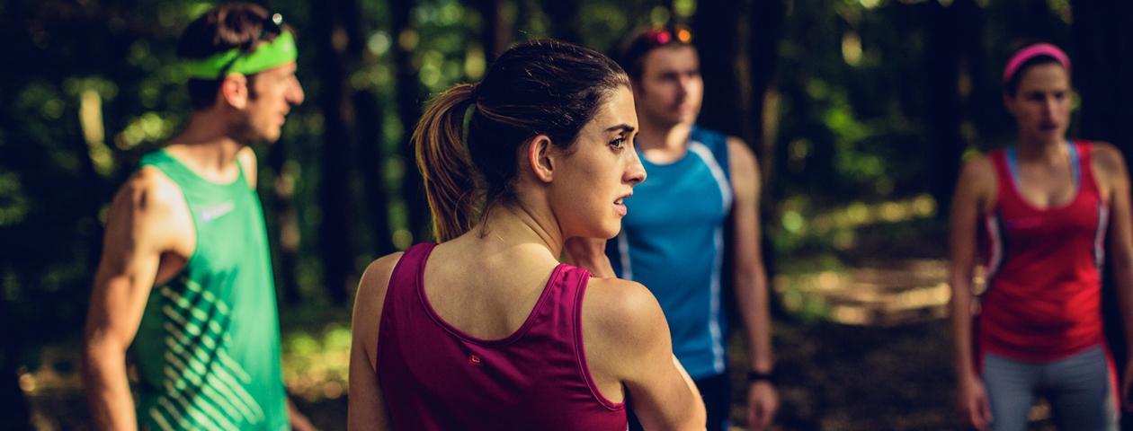 Vier Läufer in bunten bedruckten Lauftrikots im Wald