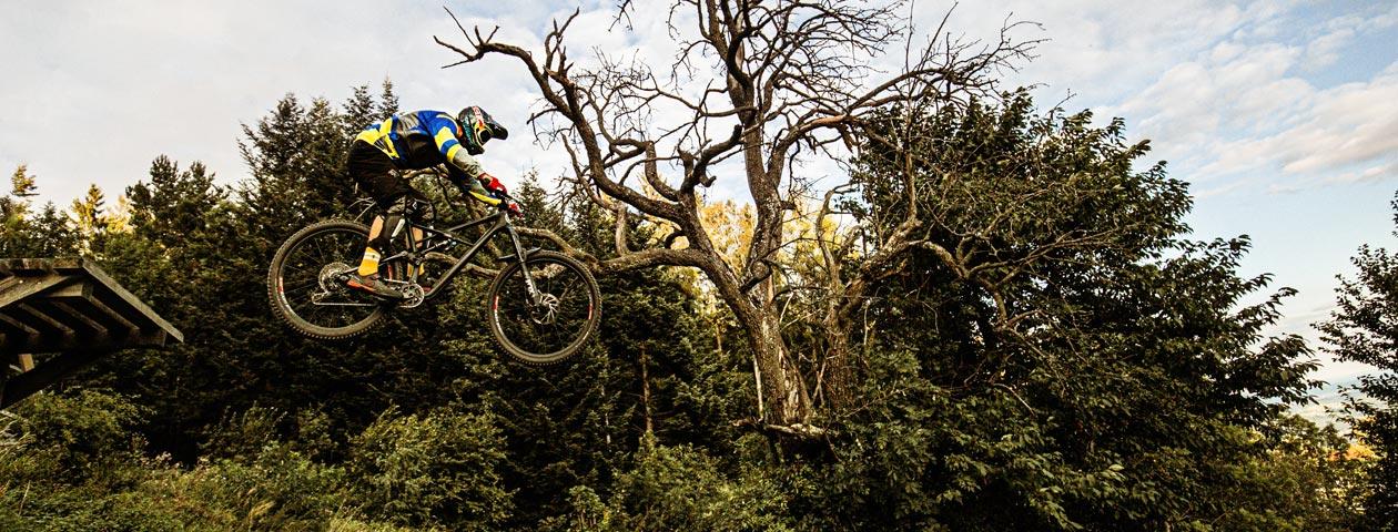 Downhill Mountainbiker springt mit selbst gestaltetem MTB-Downhill-Trikot eine Rampe hinunter