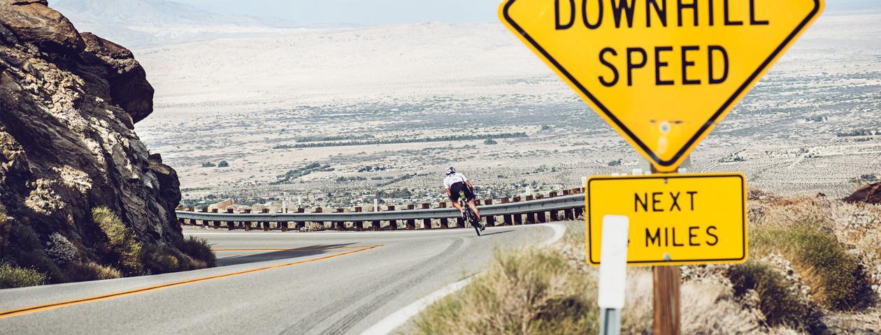 Radfahrer im individualisierten Radtrikot legt sich bergab auf einer Straße neben einem Felsen in die Kurve