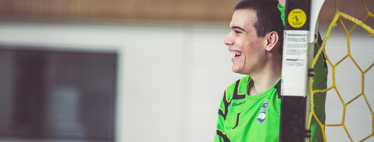 Handball goalie with green customised jersey smiling