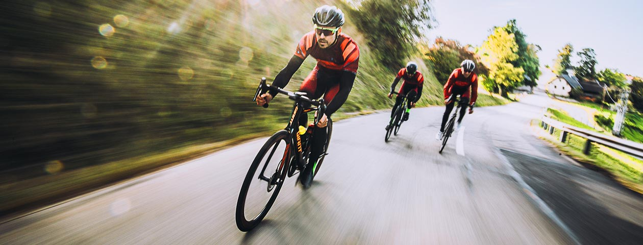 Three cyclists in custom cycling jerseys and cycling bib shorts race down the road