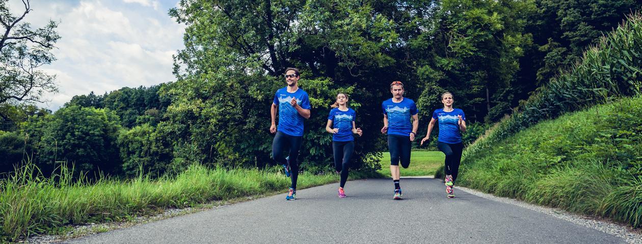 Corredores de una empresa en camisetas del color corporativo azul brillante corriendo en un camino en la naturaleza