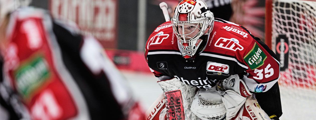 El portero de hockey sobre hielo de Kölner Haie con una camiseta negra y roja de hockey sobre hielo delante de la portería.