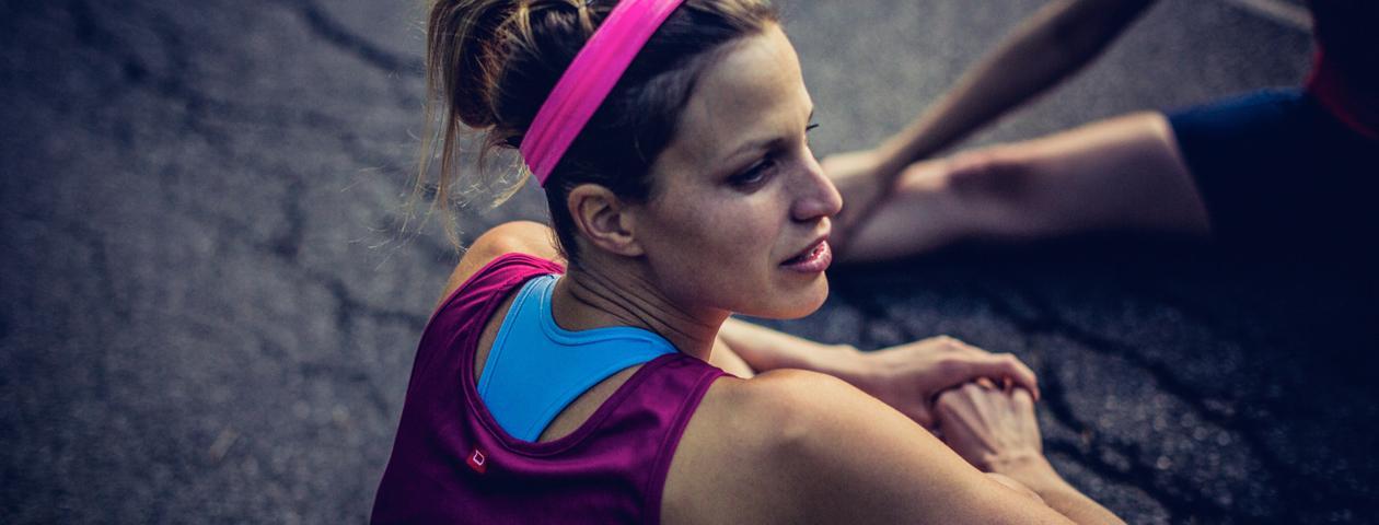 Coureuse à pied assise sur le sol et qui porte un maillot de running rose personnalisé
