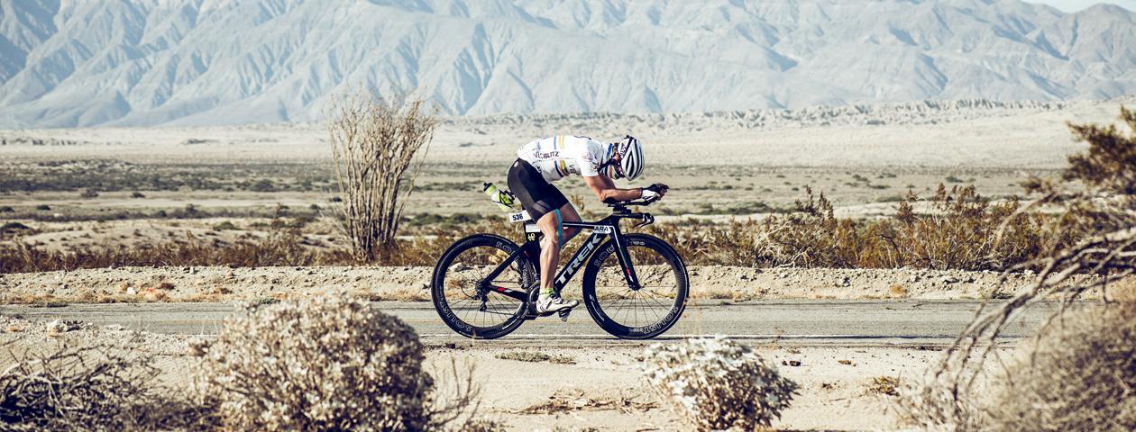 Ciclista sulla propria bicicletta nel deserto con maglia personalizzata.