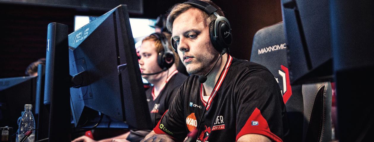 Gamer davanti al pc con maglia eSports personalizzata in rosso e nero.
