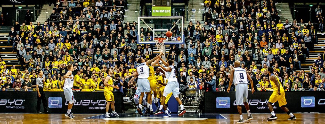 Giocatori di basket degli Eisbären Bremerhaven e degli EWE Baskets Oldenburg con maglia personalizzata owayo blu nell'uno contro uno durante il salto.